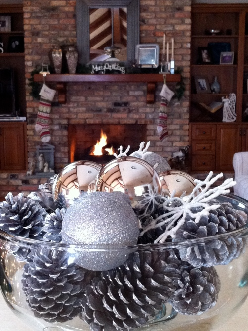 Silver spray painted pine cones with ornaments and snowflakes.